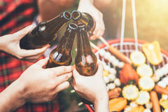 Friends clinking bottle of beer during camping party Stock Photography