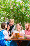 Friends clinking glasses in beer garden Royalty Free Stock Photos