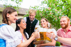 Friends clinking glasses in beer garden Stock Photography