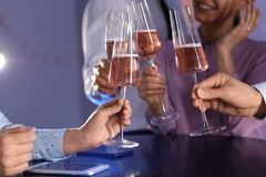 Friends clinking glasses of champagne at table in restaurant royalty free stock photos