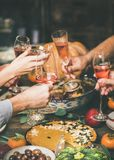 Friends clinking glasses at festive Christmas table with different snacks stock photography