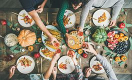 Friends clinking glasses at Thanksgiving Day with vegetarian meals royalty free stock photography