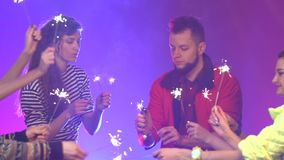 Friends at the club light the sparklers they celebrate in disco . Smoke background. Slow motion stock video footage