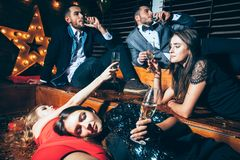 Friends at club lying on the floor and cheers after party having. Fun. Crazy party. New year, Birthday, Holiday Event concept royalty free stock image
