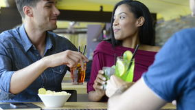 Friends at cocktail party. Portrait of happy young woman and men holding cocktail glasses. Friends drinking an alcoholic beverages at bar. Smiling girl and guys stock video