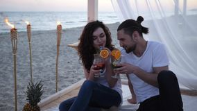 Friends with cocktail on tropics beach, loving couple having cocktail in hands, men and women mixed drink, young people. Drinking on background beautiful beach stock video footage
