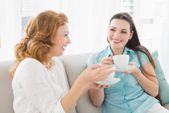 Friends with coffee cups enjoying a conversation at home Royalty Free Stock Photo