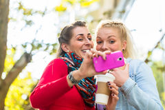Friends with coffee and phone in city Stock Photos