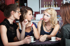 Friends in a Coffee Shop. Four young ladies converse over coffee in a cafe Royalty Free Stock Photography