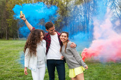 Friends with colored smoke on lawn Royalty Free Stock Photos