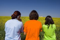 Friends with colorful tshirts. Watching the landscape full of yellow daisies Royalty Free Stock Photography