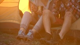 Friends in comfortable shoes sitting in tent and drinking tea, hiking in forest stock video