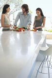 Friends Communicating While Preparing Food At Kitchen Counter. Happy multiethnic young friends communicating while preparing food at kitchen counter stock image