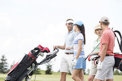 Friends communicating while walking at golf course against clear sky Stock Photos