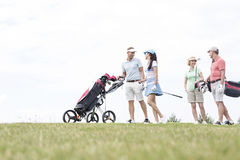 Friends communicating while walking at golf course against clear sky Royalty Free Stock Images