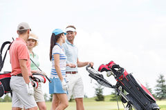 Friends communicating while walking at golf course against clear sky Stock Photo
