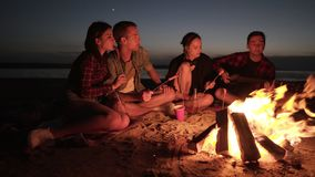 Friends company of four are hanging out on beach near the bonfire. Eating sausages, drinking, playing the guitar. Dark stock footage