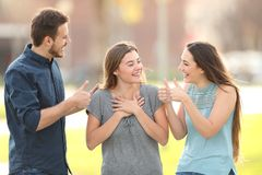Friends congratulating a happy girl in the street royalty free stock image