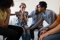 Friends consoling worried woman. Friends consoling worried women while sitting on chair in art class royalty free stock image