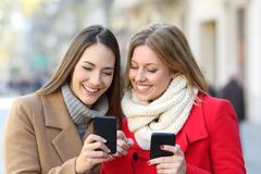 Friends consulting smart phone in the street. Friends consulting smart phone content in the street in winter stock photography