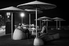 Friends Conversation in City Park at Night Stock Photography