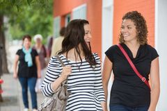Friends Conversing While Walking On Pavement. Happy female friends conversing while walking on pavement Royalty Free Stock Photography