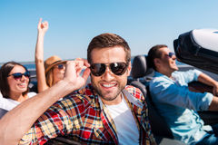 Friends in convertible. Four cheerful friends enjoying road trip in their convertible while handsome men adjusting his sunglasses and smiling Royalty Free Stock Image