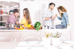 Friends cooking at home. Group of friends at home party, women cooking dinner for her guests - Young adults talking and having fun at home while preparing a Royalty Free Stock Photos