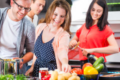 Friends cooking pasta and meat in domestic kitchen Stock Image
