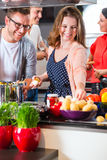 Friends cooking pasta and meat in domestic kitchen Stock Photo