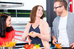 Friends cooking pasta and meat in domestic kitchen Royalty Free Stock Photography
