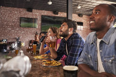 Friends At Counter In Sports Bar Watching Game Stock Photography