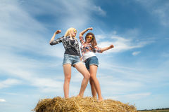 Friends on country vacations dancing on farm straw bale Royalty Free Stock Photos