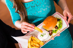Friends or couple eating fast food with burger and fries. In American fast food diner Royalty Free Stock Images