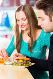 Friends or couple eating fast food with burger and fries. In American fast food diner Stock Photo