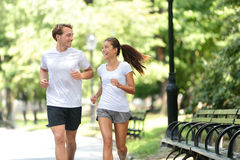 Friends couple happy running together in city park stock image
