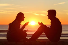 Friends or couple of teens talking at sunset. Side view of a full body of two friends or couple silhouette of teens sitting and talking at sunrise on the beach Royalty Free Stock Images