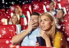 Friends or couple watching horror movie in theater Royalty Free Stock Photos