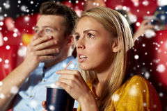 Friends or couple watching horror movie in theater Royalty Free Stock Image