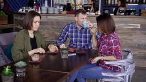 Friends with cups of coffee sitting at table stock footage
