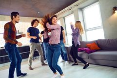 Friends dance at a student`s party in the apartment. Friends dance fun at a student`s party in the apartment Royalty Free Stock Image