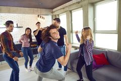 Friends dance at a student`s party in the apartment. Friends dance fun at a student`s party in the apartment Stock Image