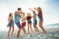 Friends dancing on the beach. On a sunny day Stock Photos