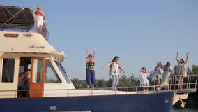Friends dancing on big expensive yacht and have fun at board on corporate party at vacation in sea. Kherson, Ukraine - 28 July 2017: rich friends dancing on big stock footage
