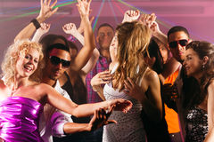 Friends dancing in club or disco. Group of friends - men and women of different ethnicity - dancing to the music in a disco club having lots of fun Stock Images