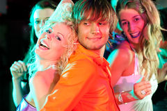 Friends dancing in club or disco. Group of friends - men and women of different ethnicity - dancing to the music in a disco club having lots of fun Royalty Free Stock Images