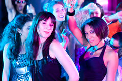 Friends dancing in club or disco. Group of friends - men and women of different ethnicity - dancing to the music in a disco club having lots of fun Stock Photos