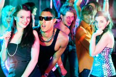 Friends dancing in club or disco. Group of friends - men and women of different ethnicity - dancing to the music in a disco club having lots of fun Stock Image
