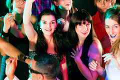 Friends dancing in club or disco. Dance action in a disco club - group of friends, men and women of different ethnicity, dancing to the music having lots of fun Royalty Free Stock Photos