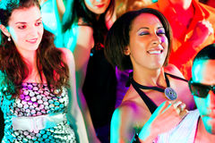 Friends dancing in club or disco. Dance action in a disco club - group of friends, men and women of different ethnicity, dancing to the music having lots of fun Stock Photos